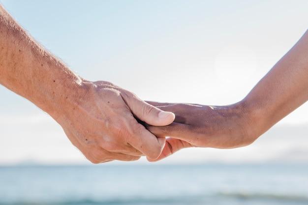 ビーチでのカップルの手の眺め