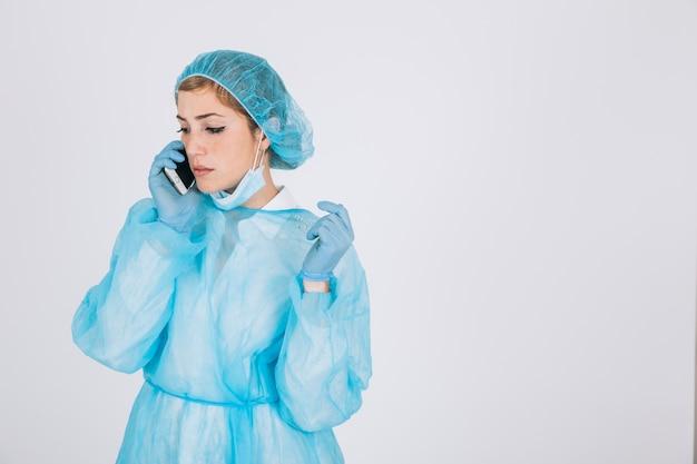 Хирург работает и разговаривает по телефону