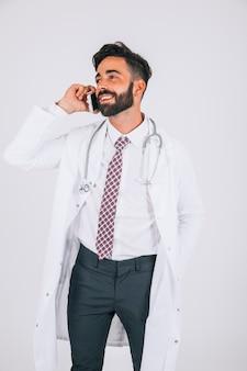 Доктор улыбается и разговаривает по телефону