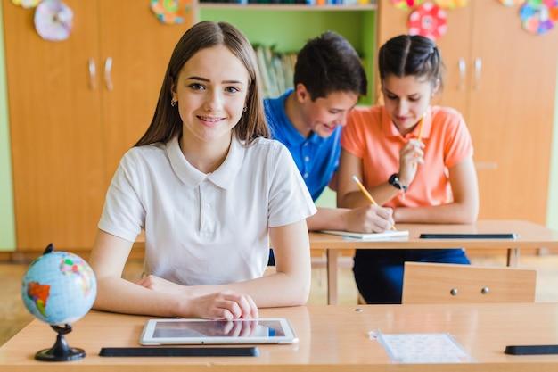 Смайлик девочка позирует в классе