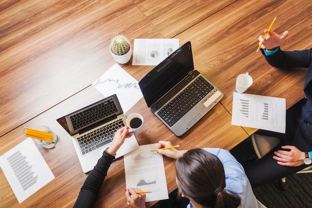 Люди, сидящие на столе с ноутбуками