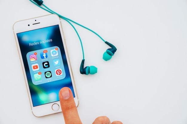 イヤホン、アプリでいっぱいの携帯電話、画面に触れる指