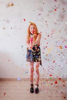 パーティーポッパーで祝う明るい女性