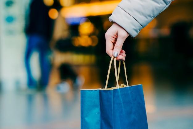女性の手はショッピングバッグを持って