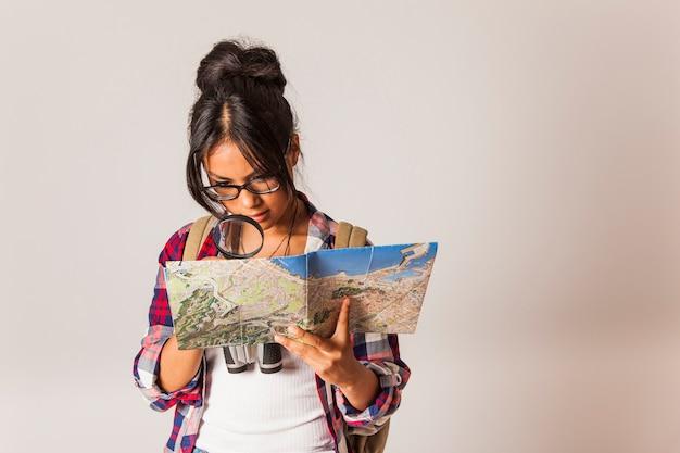 虫眼鏡を使って地図を見る観光女性