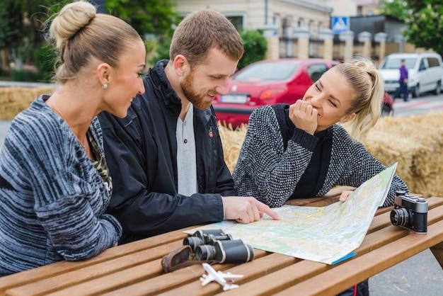 Счастливые путешественники сидят с картой