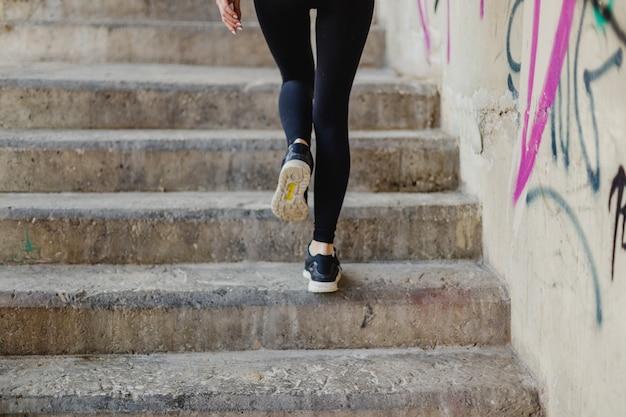 Женщина бежит вверх по лестнице снаружи