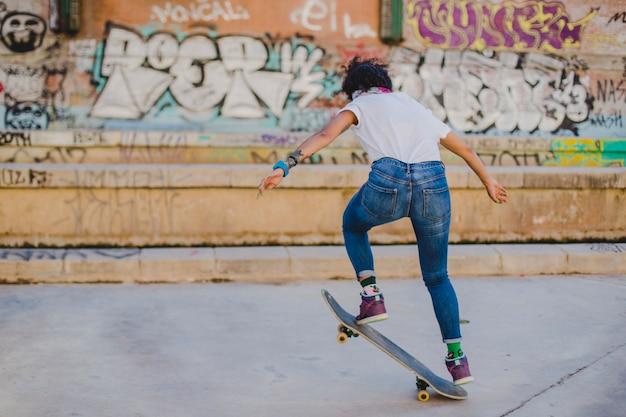 ブルネット女の子が乗ってスケートボードを作るトリック