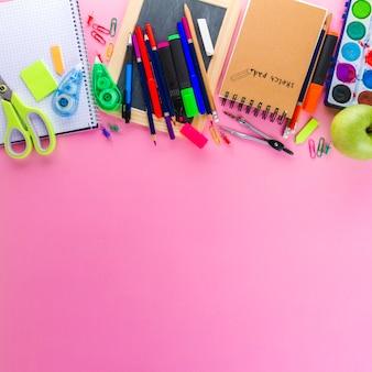 Блокноты и карандаши на розовом