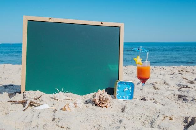 ビーチでの黒板とカクテル