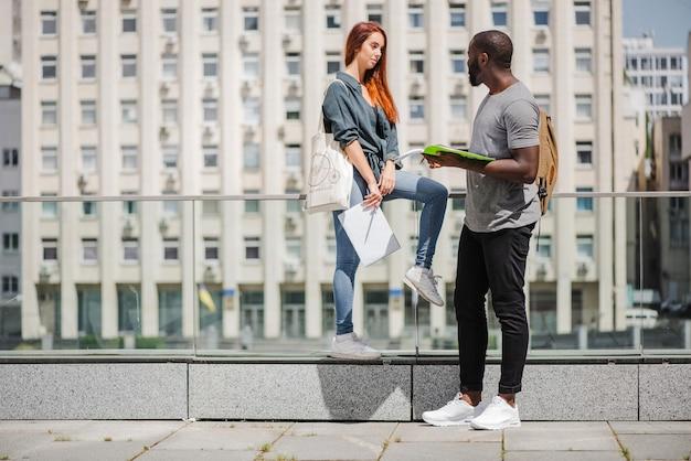ノートを持っている学生は通りで話す