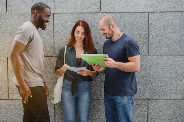Студенты, держащиеся ноутбуки, постоянно улыбаясь
