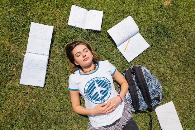 Девушка, лежащая на траве, окруженная ноутбуками