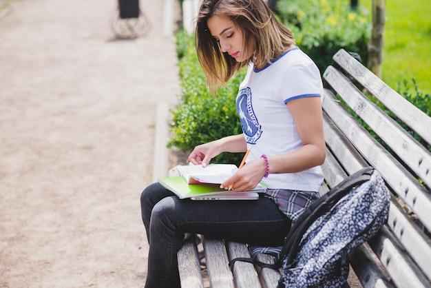 Девочка сидит на скамейке проведения ноутбуков, изучая