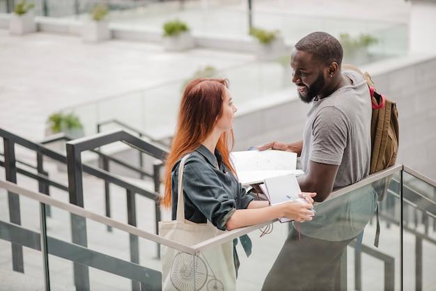 Улыбающийся мужчина и женщина с документами на лестнице