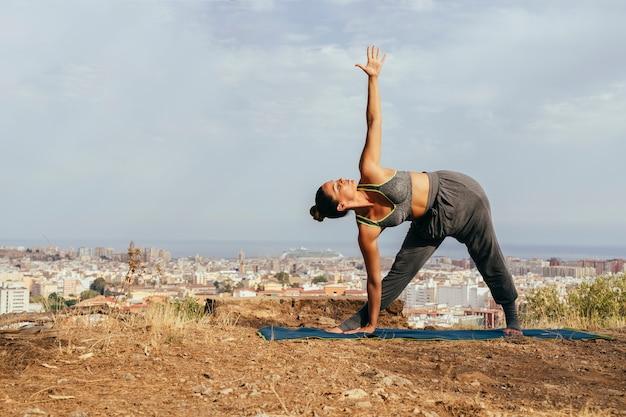 Женщина делает йогу с городом на заднем плане