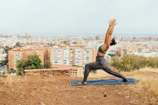 Молодая женщина в йоге и городе позади