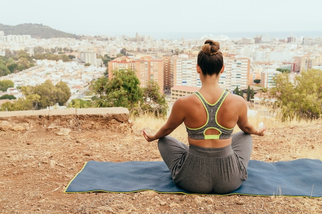 Женщина медитирует с городом на заднем плане