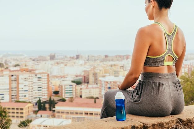 Подходящая женщина, отдыхающая с бутылкой воды и городом на заднем плане