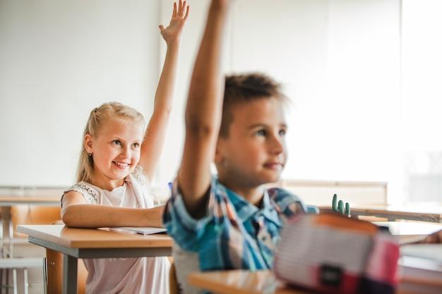 Дети, сидящие в школьных столах, поднимающие руки