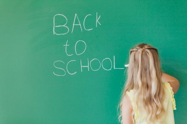 ブロンドの女の子は、黒板に書く