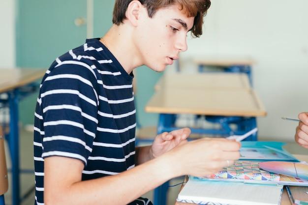 Сосредоточенный мальчик делает домашние задания в классе