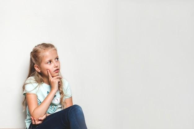 Девушка, сидящая на стене, касаясь щеки