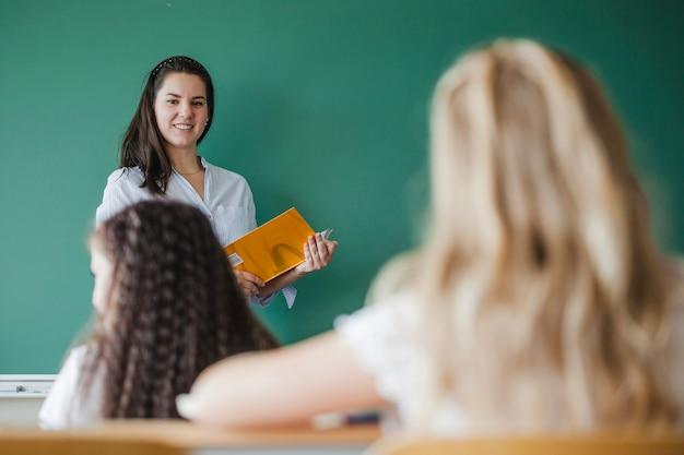 Женщина учитель стоит против зеленого доски