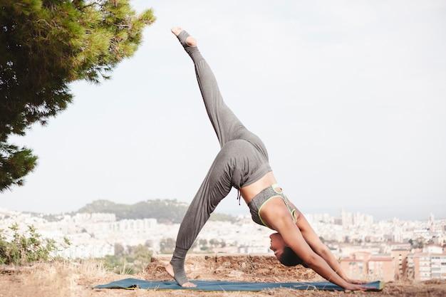 Вид сбоку женщина делает упражнения йоги с видом на город