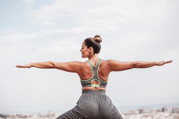 Вид сзади женщина делает упражнения баланса