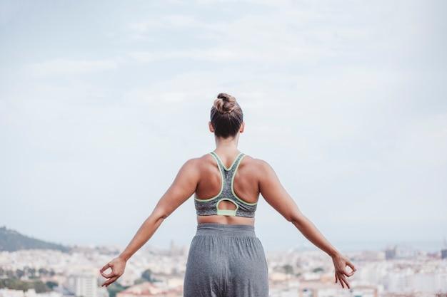 Женщина, медитируя, глядя в сторону города