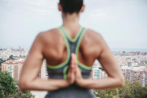Вид сзади женщина, занимающаяся медитацией перед городом