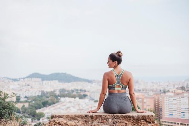Женщина, сидящая на скале в передней части города и глядя в сторону