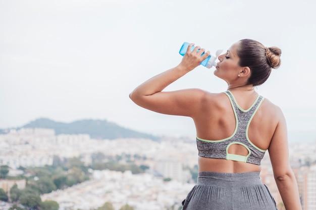 Женщина питьевой воды перед городом