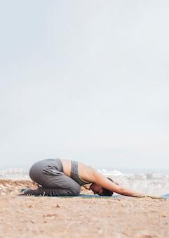 Женщина делает упражнения медитации йоги на открытом воздухе