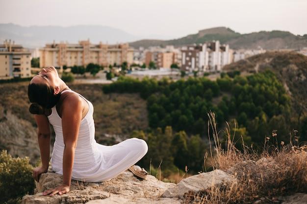 Мирная женщина на скале рядом с городом