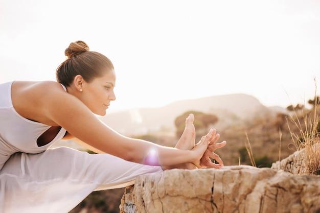 Молодая женщина, растяжение ноги на скале