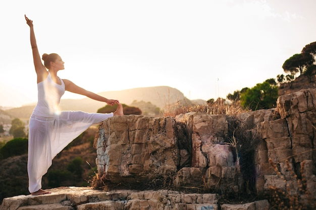 Вид сбоку молодой женщины, занимающейся йогой в природе