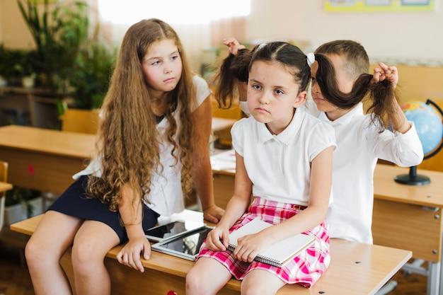 子供たち、教室、机の上に座る