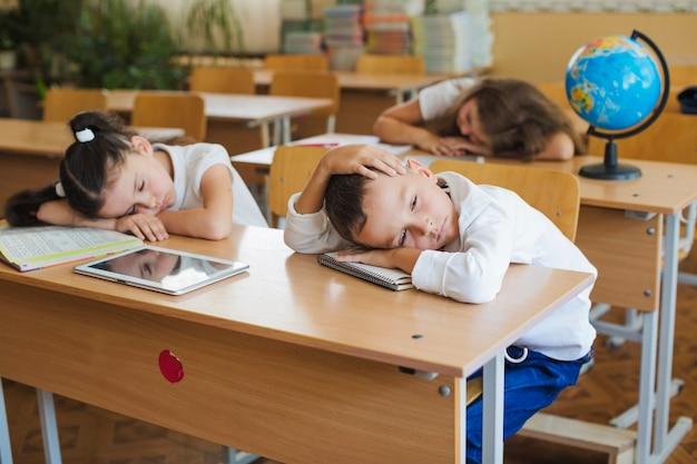机の上に横たわっている児童