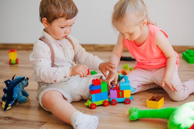 床に玩具を持つ子供たち