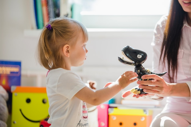 女の子に恐竜を与える女性