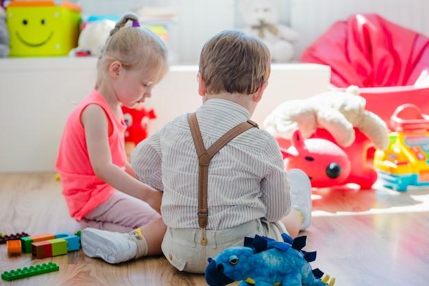 プレイルームの床に座っている子供たち