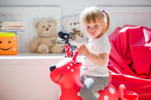 鹿のおもちゃに座っている少女