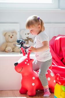 赤い鹿のおもちゃに座っている少女