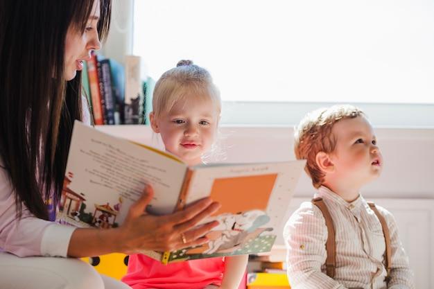 ベビーシッターは少女に本を示している