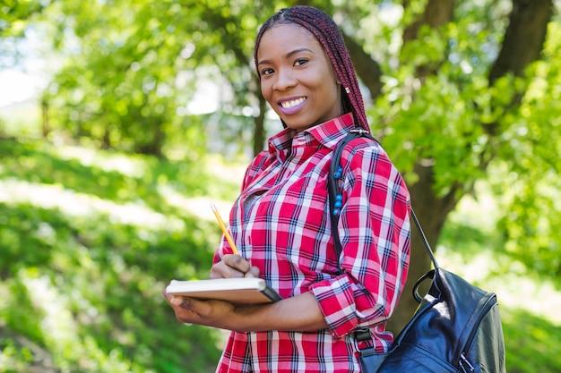 Черная девочка позирует с блокнотами