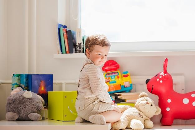窓のおもちゃで座っている男の子