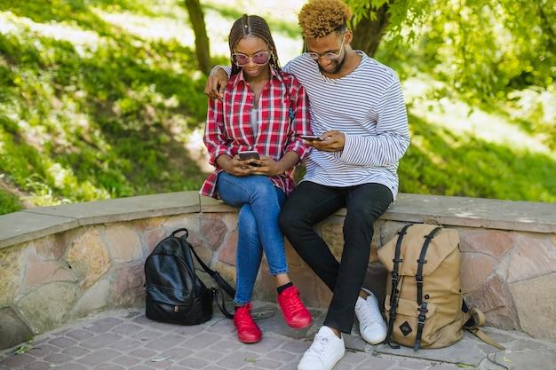 公園でスマートフォンを使用している若者
