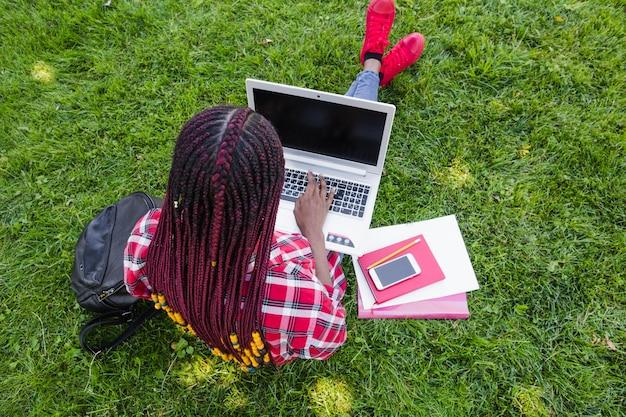芝生でコンピュータで勉強している匿名の女性